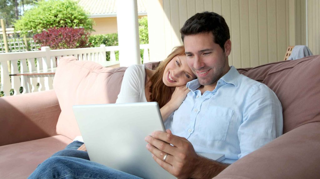 Couple sitting in couch with laptop computer